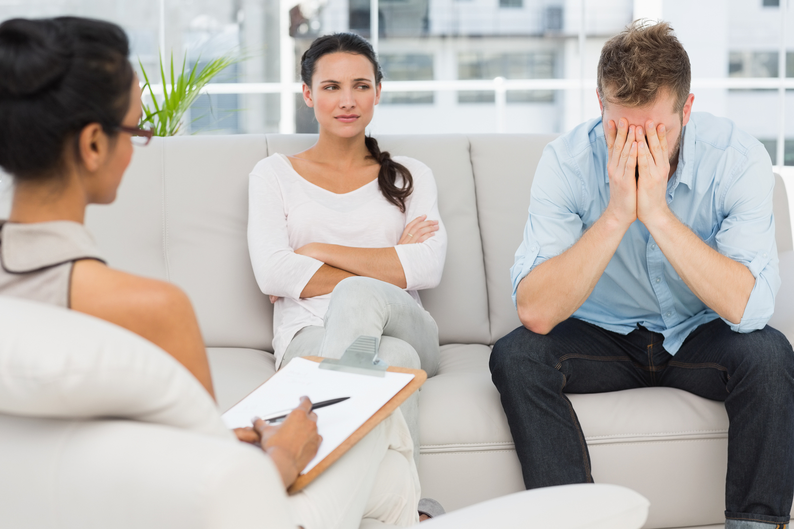 Unhappy couple sitting on sofa at therapy session in therapists