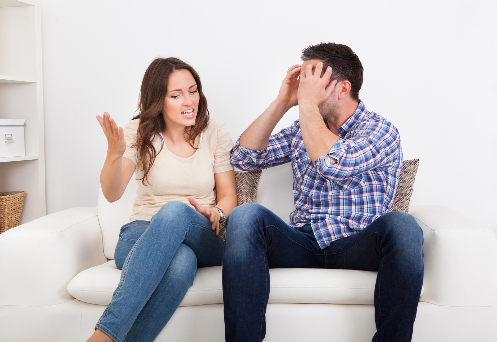 Portrait Of Frustrated Couple Sitting On Couch Quarreling With Each Other